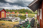 Fishing houses on the Archipelago Sea with bikes parked in the foreground, Finland