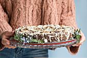 Frau hält veganen Schokoladenkuchen mit weisser Schokolade