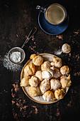 Mini-Donuts mit Puderzucker und Tasse Kaffee