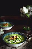 Green pea soup with parsley, cream and croutons