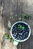 Bilberry in the cup on a wooden background