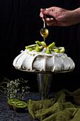 Preparing pavlova with coconut cream kiwi and passion fruit sauce