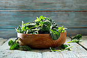 Mini pak choi leaves in a wooden bowl