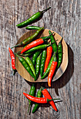 Red and green chili peppers on a wooden plate