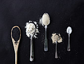 Verschiedene Backzutaten auf Löffeln: Mohn, Mehl, Zucker, Hefe und Salz
