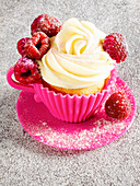 Cupcake with a buttercream rose and raspberries