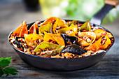 Colorful conchiglioni arlecchino with bolognese sauce