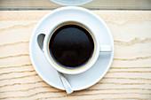Tasse schwarzer Filterkaffee auf Holzuntergrund