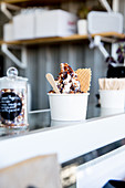 Soft ice cream with chocolate sauce in a paper cup on a sales counter