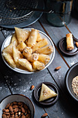 Sweet samosas and rolls with cream filling, honey glaze and almonds (Tunisia)