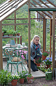 Frau holt Töpfe mit Nelken aus dem Gewächshaus