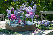 Sträuße mit Rosenblüten und Flieder in Holzkiste, Kranz aus Gräsern
