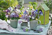 Kleine Sträuße aus Akelei, Flieder, Rosen und Hornkraut in Tassen