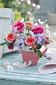Strauß aus Rosen, Flieder und Hornkraut in Tasse