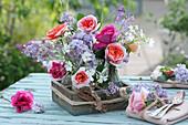 Kleine Sträuße mit Rosen, Flieder und Hornkraut als Tischdeko