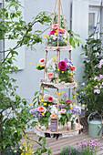 Selbstgebaute Etagere aus Birkenscheiben: Sträuße aus Rosen, Flieder und Hahnenfuß