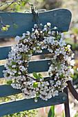 Kranz aus Blütenzweigen vom Zierapfel an Stuhllehne