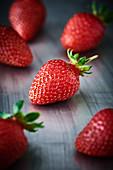 Close Up einer Erdbeere auf einer Metallplatte. Um diese Erdbeere liegen noch 5 andere Erdbeeren