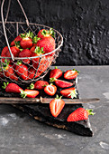 Fresh strawberries in a wire basket and cut in half on a stone slab