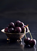 Cherries with drops of water in a silver bowl
