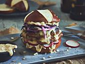 Laugenbrötchen-Burger mit Schweinefleisch, Käse und Zwiebeln