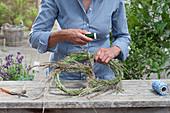 Riesenbrezel aus Gras binden\nFrau biegt mit Draht versteiftes und umwickeltes Bund aus Gräsern in Brezelform und fixiert mit Wickeldraht