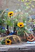 Sträuße aus Sonnenblumen, Jungfer im Grünen und Getreideähren in antikem Gläsertablett, Brezeln, Bierkrüge, Teller und Besteck