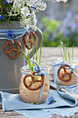 Obatzder in kleinen Einmachgläschen, dekoriert mit Brezeln und Schnittlauch