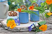 Becher mit Obatzder, Brezeln, Schnittlauch, Blüten von Kapuzinerkresse und Hornveilchen auf Holzbrett aus Birkenholz