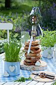 Selbstgebauter Brezenturm aus Holzscheibe und Ast, dekoriert mit Kräuter-Kränzchen, Bändern, Birkenscheibe mit Aufschrift Servus und Holz-Herz