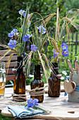 Tischdekoration mit Storchschnabel und Getreideähren in Bierflaschen, Besteck im Bierkrug mit Holz-Herz als Deko