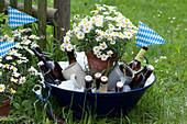 Bierflaschen und Krügen in Schüssel mit Eiswürfeln, Topf mit Margerite, bayrische Wimpel als Deko