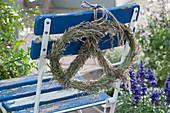 Brezel aus Gräserblüten an Stuhllehne