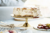 Rhubarb crumble cake with vanilla cream on a golden cake stand