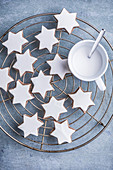 Several cinnamon stars and a cup of eggnog on a cooling grill