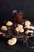 In Schokolade getunkte Mandelkipferl auf Abkühlgitter