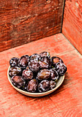 Several plums in a stone bowl on a red wooden plate