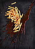 Big blob of ketchup with french fries and salt on a black background
