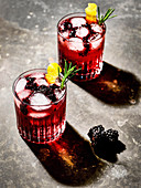 Two glasses of gin and tonic with blackberry juice, blackberries, ice cubes, lemon zest and rosemary