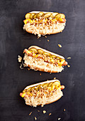Three hot dogs with cooked sausages, sauerkraut, pickled cucumbers, mustard and roasted onions