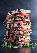 Gestapelte Roggenmischbrot-Sandwiches mit Salami, Tomaten und Rucola