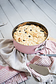 Blueberry crumble cake in a pink baking pan