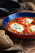 Shakshuka in a pan on an olive wood plate with bread (Tunisia)