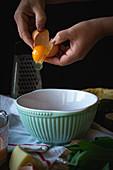 Ei in Schüssel aufschlagen