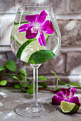 A glass of sparkling water with lime and an edible flower garnish, sitting on an outdoor table with greenery