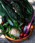 Wooden bowl filled with vegetables and herbs - rainbow swiss chard, leeks, tomatoes, zucchini, onion, garlic, mint and basil