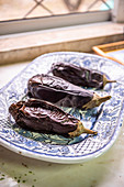 Roasted aubergines on a blue tray