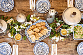 Table spread and setting with blue crockery and rustic props and homemade bread in the center