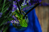 Summer detox lemonade with lavender, lemon and mint in vintage glass with straw on rustic background with copy space