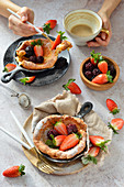 Dutch baby pancakes with strawberries and blackberries coffee mug hands